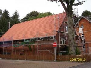Backsteinhaus mit rotem Dach und Baugerüst