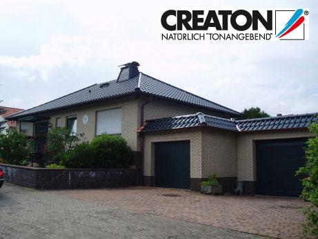 Beiges Haus mit schwarzem Dach, oben rechts das Creaton Logo