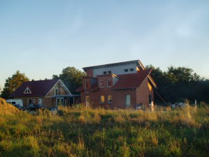 Zwei Häuser; davor eine Wiese