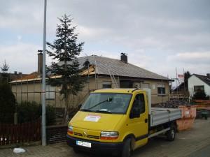 Beiges Haus mit freigelegtem Dach; davor ein Hannig Firmenfahrzeug