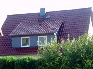 Weißes Haus mit dunkelrotem Dach