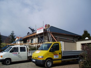 Beiges Haus mit schwarzem Dach; davor Hannig Firmenfahrzeuge