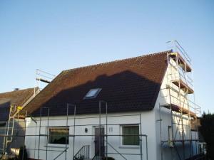 Weißes Haus mit braunem Dach und Baugerüst