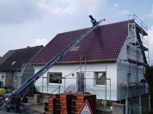 Ein Dachdeckeraufzug bringt die Pfannen aufs Dach