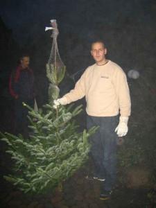Ein Mitarbeiter hält einen Tannenbaum