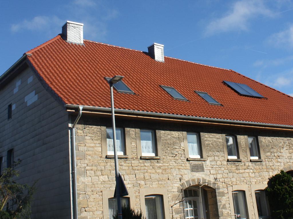 Beiges Haus mit Steinfassade und rotem Dach